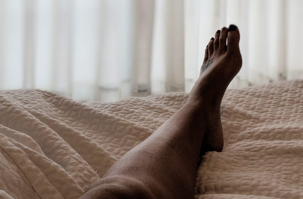 leg in bed with beige blanket